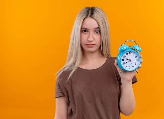 コピースペースと孤立したオレンジ色の壁に目覚まし時計を保持している若いブロンドの女の子