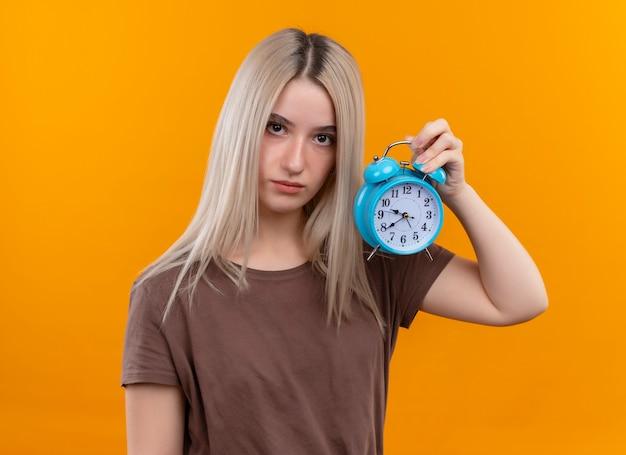 孤立したオレンジ色の壁に目覚まし時計を保持している若いブロンドの女の子