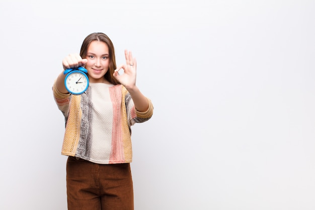 Young blonde girl holding an alarm clock on white wall