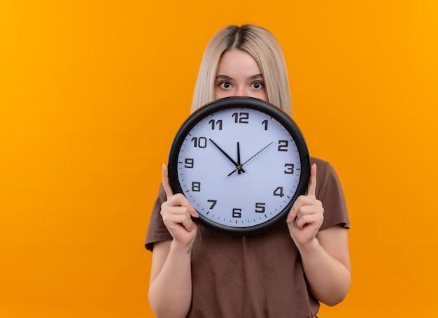 Giovane ragazza bionda che tiene l'orologio che si nasconde dietro di esso sulla parete arancione isolata con lo spazio della copia