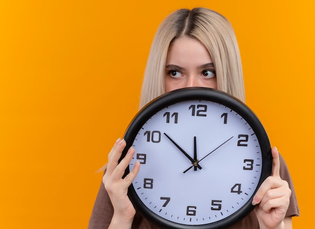 Young blonde girl holding clock hiding behind it looking at left side on isolated orange wall with copy space