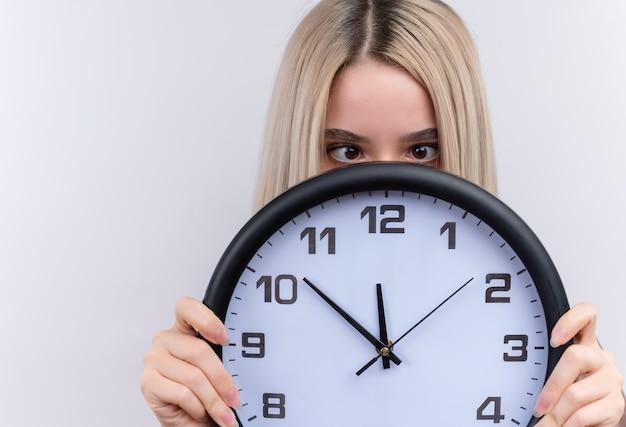 Giovane ragazza bionda che tiene orologio e nascondersi dietro di esso con gli occhi incrociati sulla parete bianca isolata con lo spazio della copia