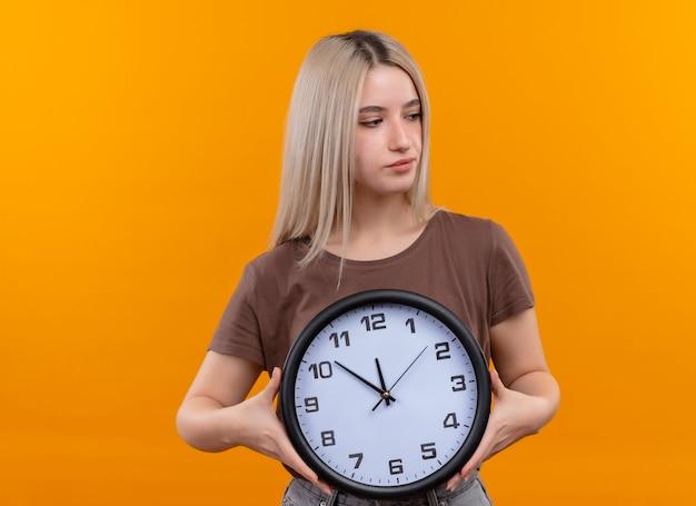 Giovane ragazza bionda che tiene orologio guardando il lato destro sulla parete arancione isolata con lo spazio della copia