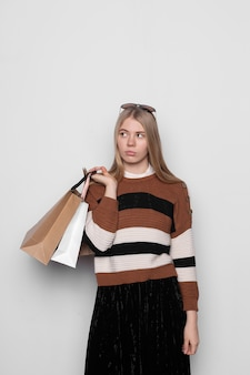 Young blonde girl holds paper shopping bags in her hands, looks bewildered and upset on white