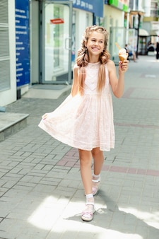 Молодая блондинка в розовом платье с косичками держит в руках мороженое