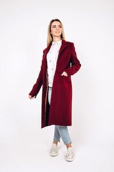 白地に赤いコートを着た若いブロンドの女の子