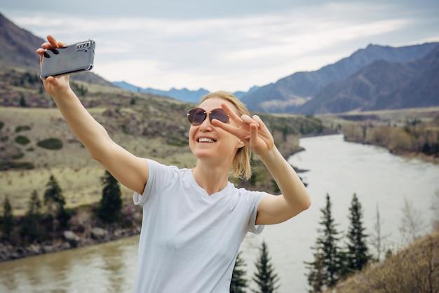 Молодая блондинка в солнечных очках и белой футболке делает селфи на своем смартфоне на фоне реки и скалистых гор. счастливый женский турист улыбается на камеру мобильного телефона.