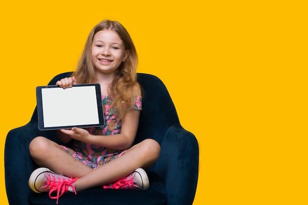 젊은 금발의 여자는 여유 공간이있는 노란색 스튜디오 벽에 흰색 화면이 미소와 함께 디지털 태블릿을 카메라에 보이고있다