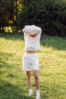 若いブロンドの女の子は笑顔で森の中を歩いて白いパーカーを着ています