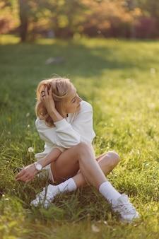 若いブロンドの女の子は笑顔で森の中を歩いて白いパーカーを着ています 無料写真