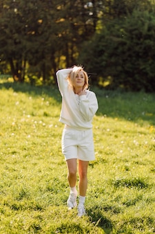 Young blonde girl is wearing a white hoodie smiling and walking in the woods