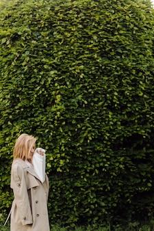 年轻的金发女孩穿着一个白色连帽衫微笑和走在森林里