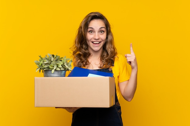 Young blonde girl making a move while picking up a box full of things pointing up a great idea