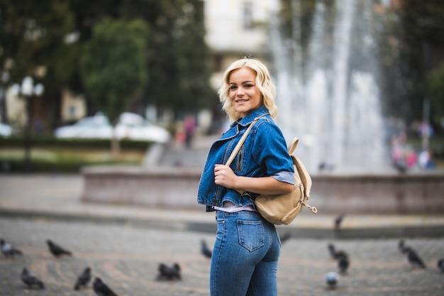 Молодая блондинка на уличном квадратном фонтане, одетая в синие джинсы с сумкой на плече в солнечный день