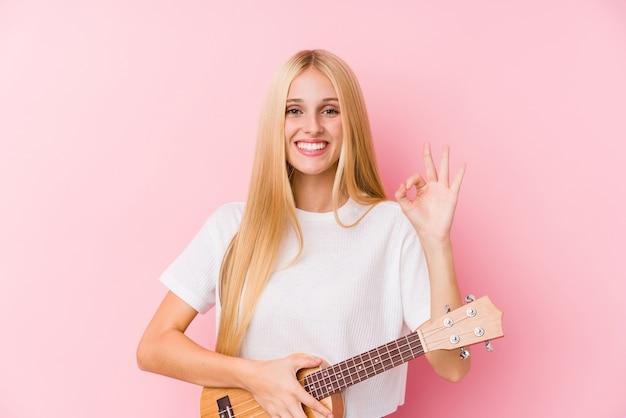 Молодая белокурая девушка играет на укелеле, веселая и уверенная, показывая хорошо жест.