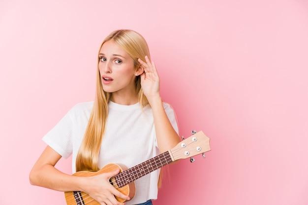 Молодая блондинка играет на укелеле, пытаясь слушать сплетни.