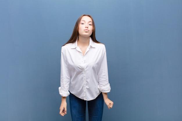 コンクリートの壁にキスを送信するかわいい、楽しく、幸せ、素敵な表情で唇を押す若いブロンドの女の子