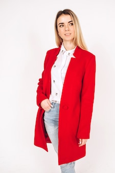 Young blonde girl in a red coat on a white