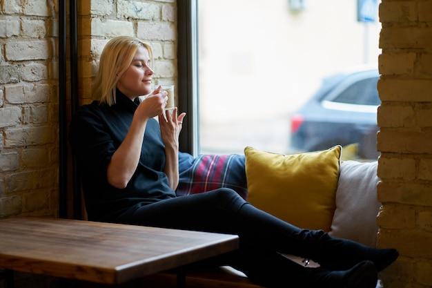 Молодая белокурая девушка распологая около окна и выпивая кофе в кафе. время расслабиться.