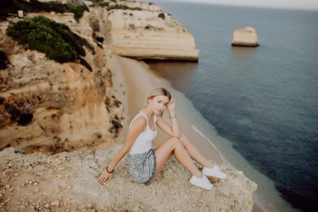 Young blonde girl sitting on the edge of the cliff looking into the ocean.