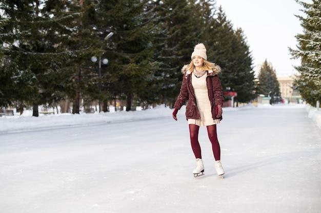 雪に覆われた冬の公園でスケートをしている若いブロンドの女の子。