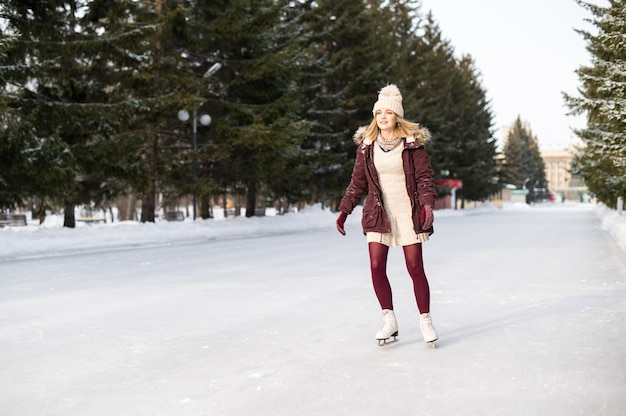 Young blonde girl skating in snowy winter park.