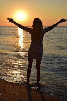 A young blonde girl stands on the beach and looks at the sun with her arms outstretched.