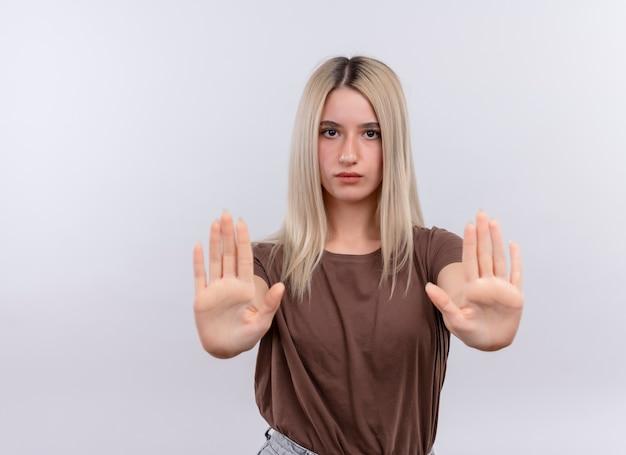 Giovane ragazza bionda che allunga le mani che gesturing fermata sulla parete bianca isolata con lo spazio della copia