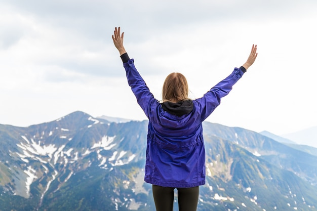 Young blonde girl travelerin a blue jacket raised her hands up and enjoying the green mountain scenery
