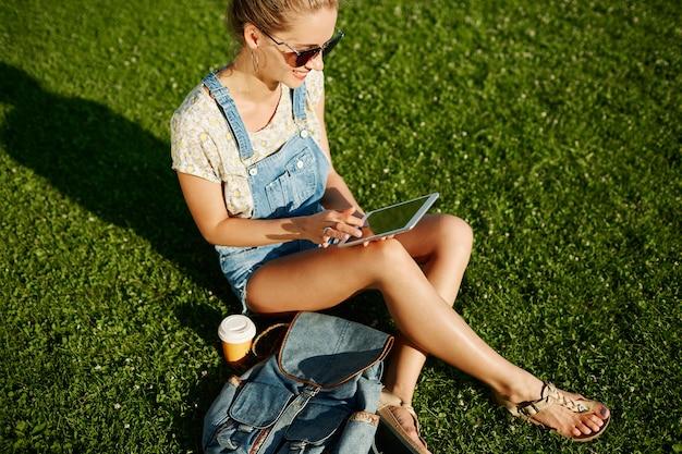 草の上に座って屋外タブレットを使用して若いブロンドの女の子
