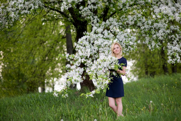 Молодая блондинка с цветком за ухом смотрит в сторону цветущей розовой яблони и улыбается. закройте проведение цветущей ветки