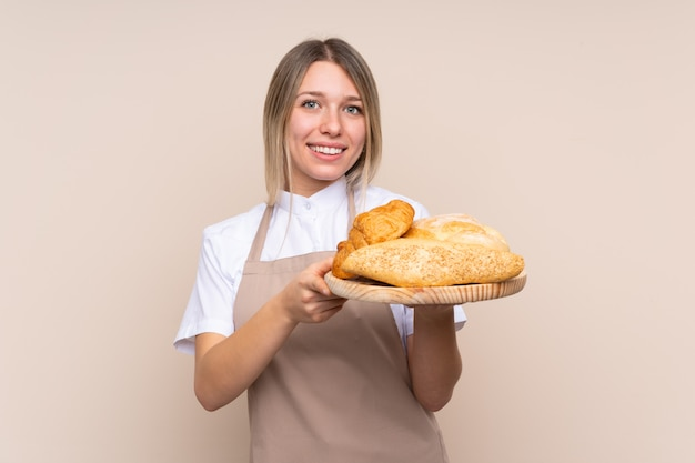 Young blonde girl with apron. female baker holding a table with several breads with happy expression