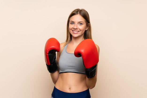 Young blonde girl with boxing gloves over isolated wall
