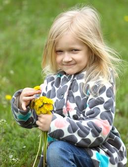 緑の芝生にタンポポの束を持つ若いブロンドの女の子