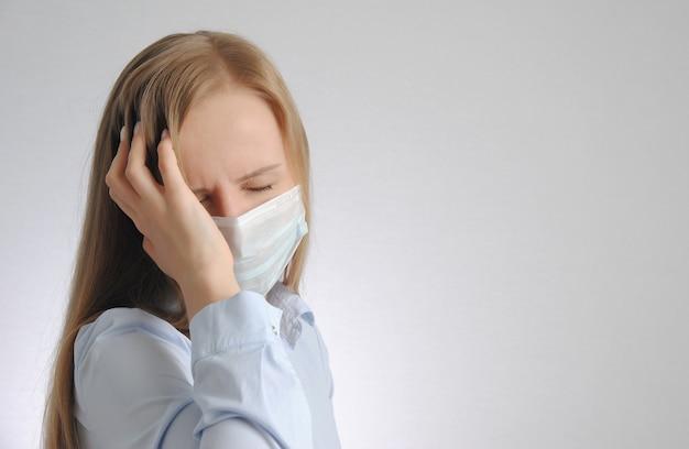 Молодая блондинка с головной болью в медицинской маске держит голову
