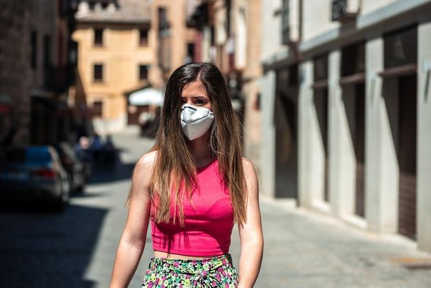긴 머리와 얼굴 마스크 도시를 걷는 젊은 금발 소녀. 유행성 시대의 관광 개념.