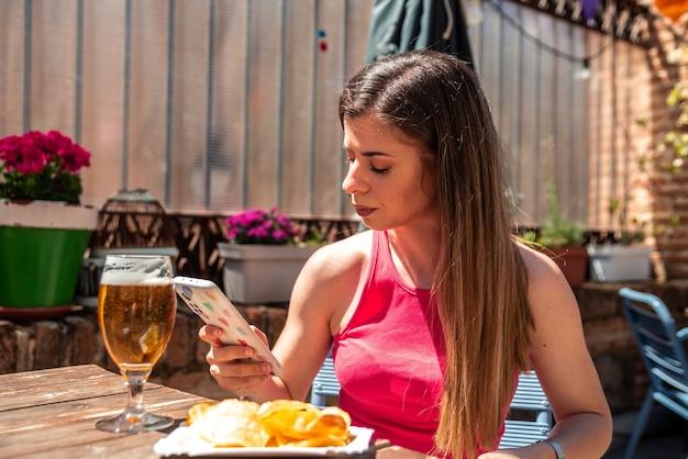 맥주를 마시고 바의 테라스에서 타파를 먹고 긴 머리를 가진 젊은 금발 소녀.
