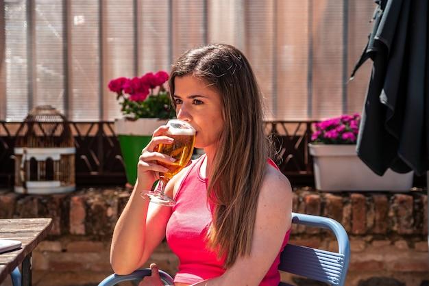 바의 테라스에서 맥주를 마시는 긴 머리를 가진 젊은 금발 소녀.