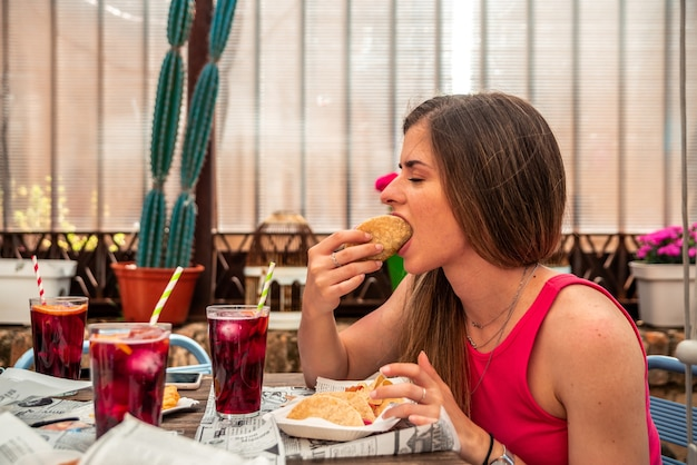 レストランのテラスでタコスを食べ、ワインを飲む長い髪の若いブロンドの女の子。