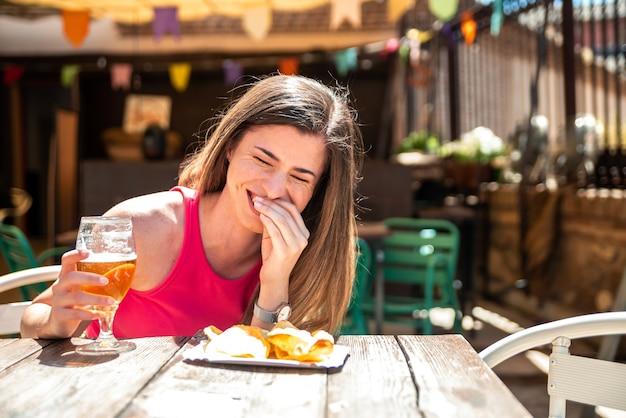 바의 테라스에서 맥주와 일부 칩을하면서 웃 긴 머리를 가진 젊은 금발 소녀.
