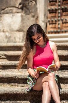 도시에서 책을 읽고 긴 머리를 가진 젊은 금발 소녀. 계단에 앉아.