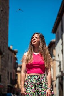도시에서 관광하는 긴 머리를 가진 젊은 금발 소녀.