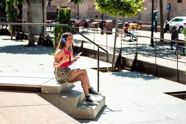 그녀의 휴대 전화와 헤드폰으로 음악을 들으면서 도시 공간에 앉아 긴 머리를 가진 젊은 금발 소녀. 그녀의 손에 커피 한 잔을 들고.