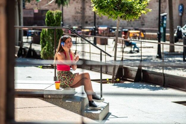 그녀의 휴대 전화와 헤드폰으로 음악을 들으면서 도시 공간에 앉아 긴 머리를 가진 젊은 금발 소녀.