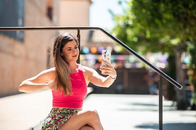 그녀의 휴대 전화로 사진을 찍는 동안 도시 공간에 앉아 긴 머리를 가진 젊은 금발 소녀. 젊은 사람과 소셜 네트워크 개념.