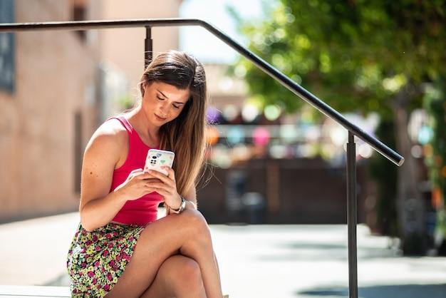 그녀의 휴대 전화를 사용하는 동안 도시 공간에 앉아 긴 머리를 가진 젊은 금발 소녀.