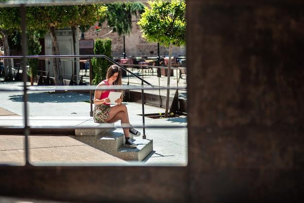그녀의 태블릿을 사용하는 동안 도시 공간에 앉아 긴 머리를 가진 젊은 금발 소녀.
