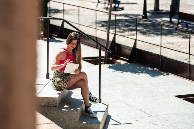 그녀의 태블릿을 사용하는 동안 도시 공간에 앉아 긴 머리를 가진 젊은 금발 소녀. 프리미엄 사진