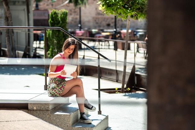 그녀의 태블릿으로 작업하는 동안 도시 공간에 앉아 긴 머리를 가진 젊은 금발 소녀.