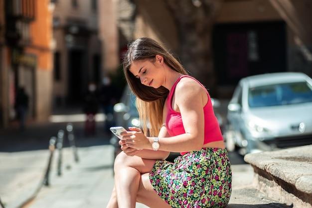 도시에있는 계단에 앉아 긴 머리를 가진 젊은 금발 소녀. 그녀의 휴대 전화에서 검색합니다.